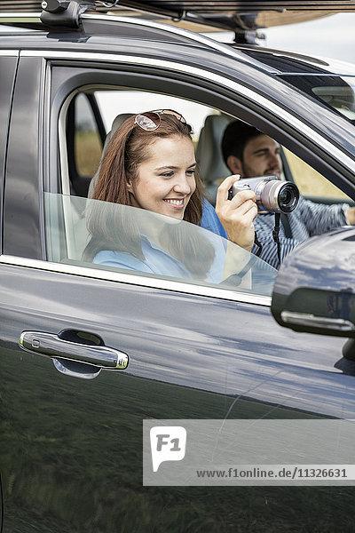 Paarfahren im Auto  Frau mit Kamera