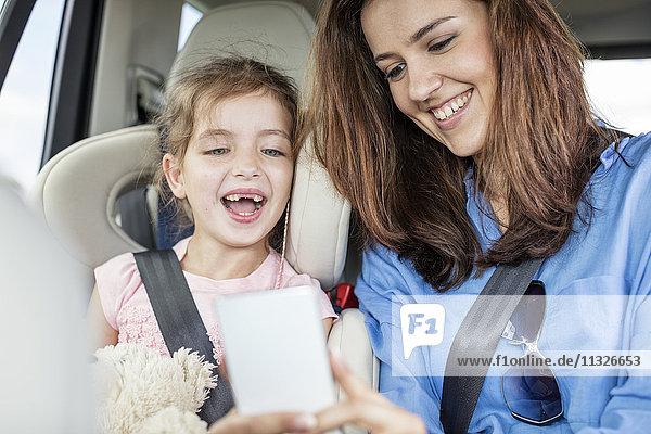 Mutter und Tochter auf Roadtrip im Auto sitzend  mit Blick auf Smartphone