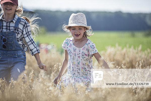 Zwei lachende Mädchen  die im Feld rennen.