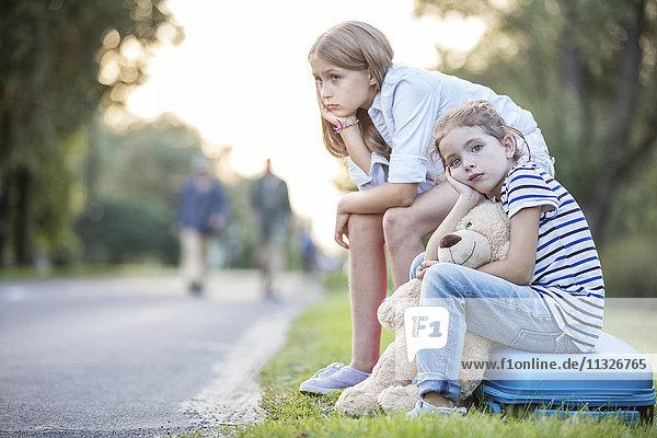 Zwei Mädchen sitzen auf dem Koffer am Straßenrand