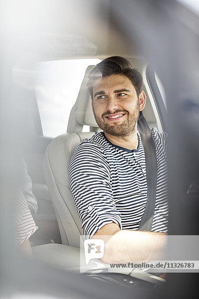 Mittlerer erwachsener Mann beim Autofahren