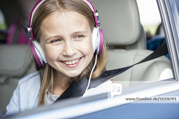 Mädchen im Auto sitzend  aus dem Fenster schauend  Musik hörend