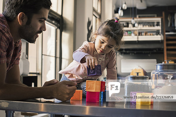 Vater und Tochter spielen mit Bausteinen