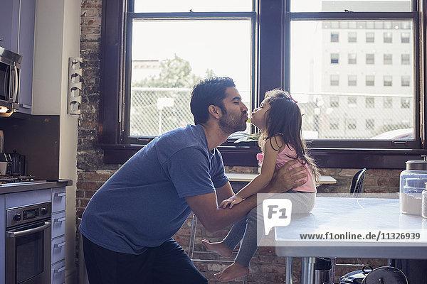 Vater und Tochter küssen sich in der Küche
