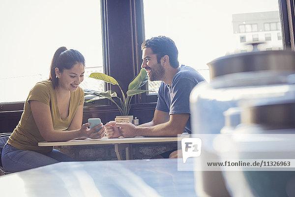 Junges Paar in der Küche mit Smartphone