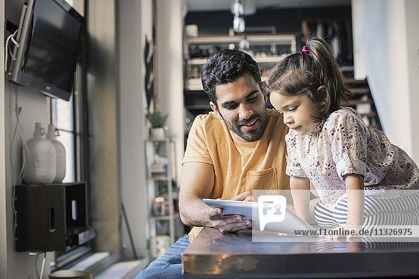 Vater und Tochter mit digitalem Tablett