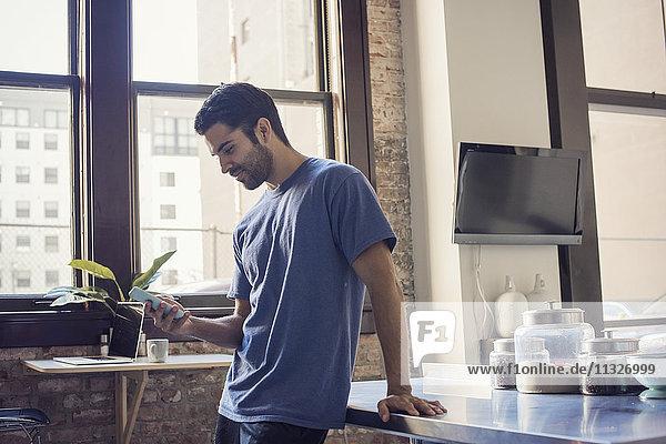 Junger Mann steht in der Küche mit Smartphone