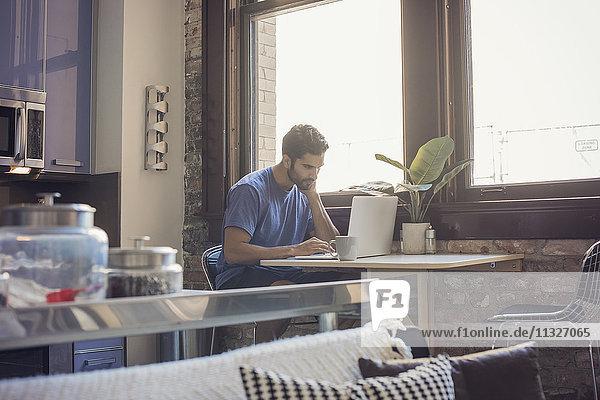Junger Mann steht in der Küche mit Laptop