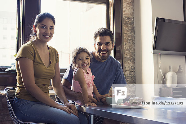 Familiy sitting in kitchen  looking at camera