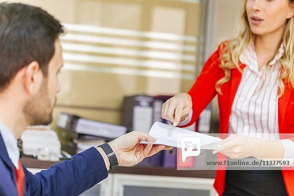 Sekretärin übergibt Dokument an Geschäftsmann im Amt