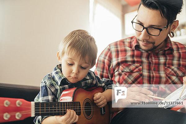 Vater und Sohn spielen Spielzeugmusikinstrumente
