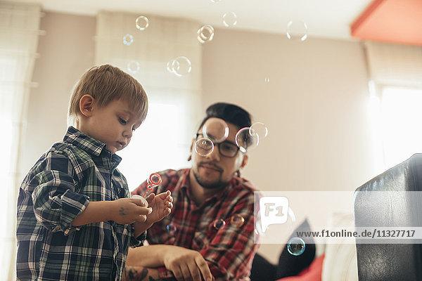 Vater und Sohn blasen Seifenblasen nach Hause
