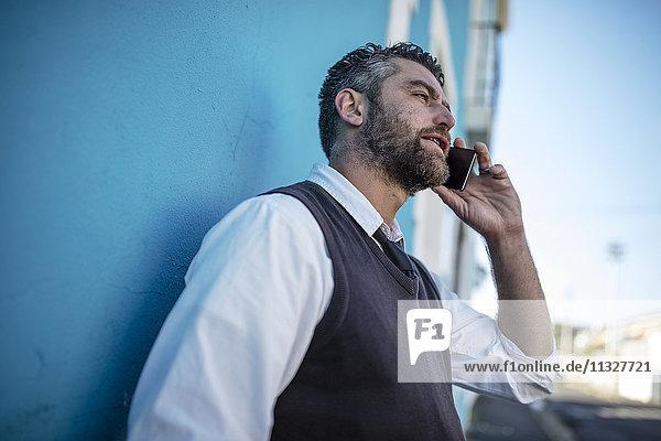 Mann lehnt sich an die blaue Wand und spricht mit dem Handy