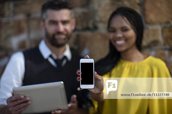 Mann hält Tablette  Frau hält Handy