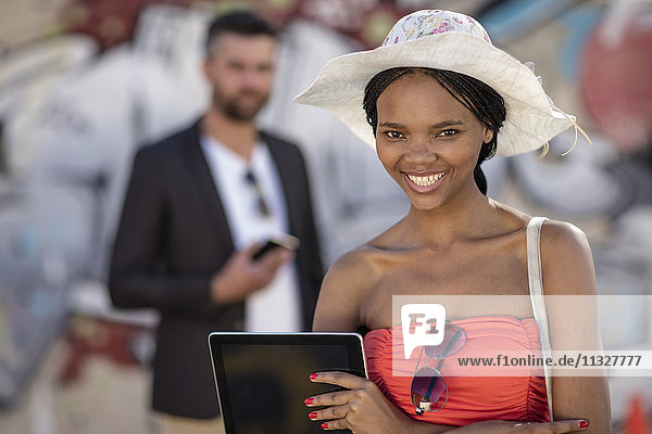Smiling woman holding a tablet outdoors