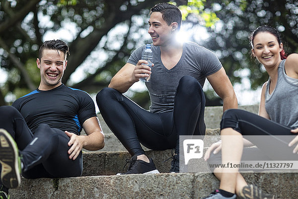Friends taking a break in fitness park  sitting on stairs