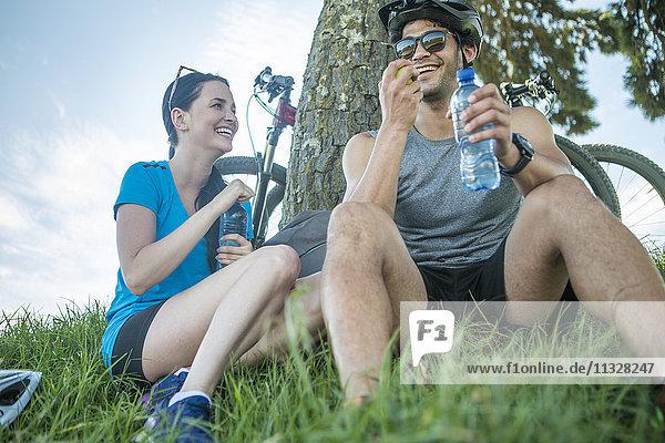 Junges Paar Mountainbiken in der Natur  Pause unter dem Baum