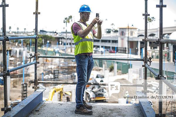 Bauarbeiter auf der Baustelle beim Fotografieren mit dem Smartphone