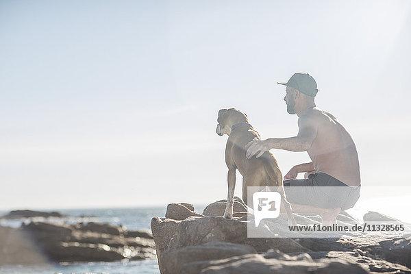 Junger Mann mit Hund am Strand