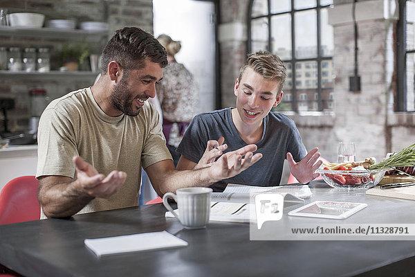 Vater hilft dem Sohn bei den Hausaufgaben in der Küche