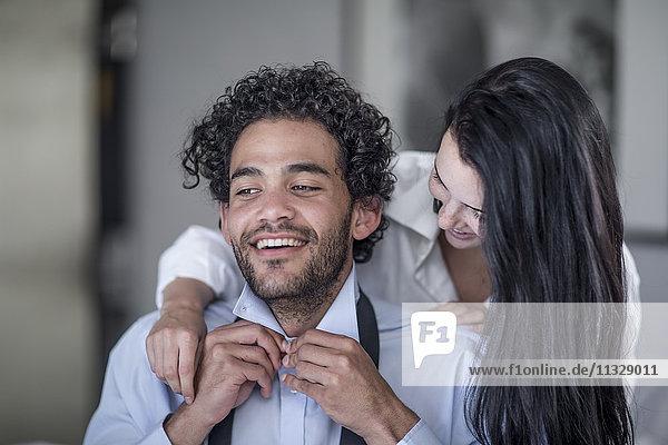 Junger Mann  der sein Hemd zuknöpft  während seine Frau ihn beobachtet.