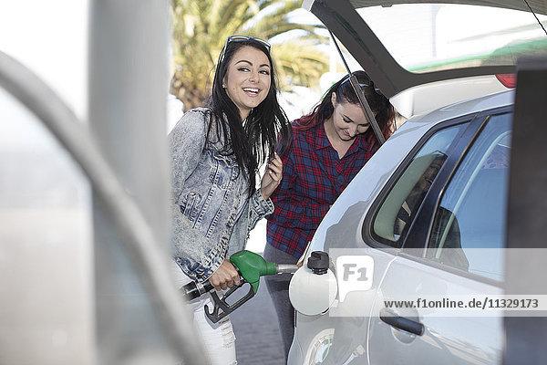 Zwei Frauen tanken Auto an der Tankstelle