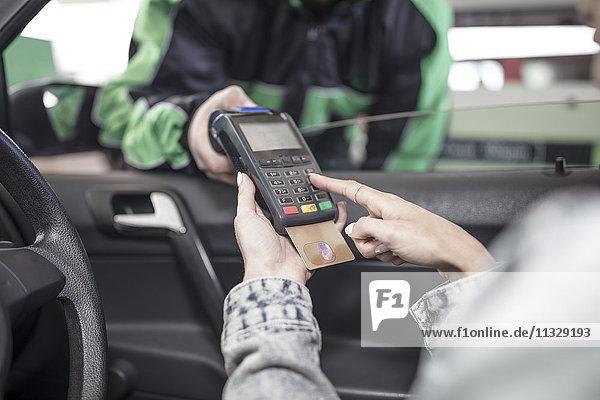Kundin bezahlt mit Kreditkarte an der Tankstelle