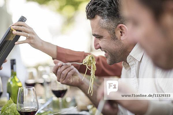 Mann isst Spaghetti zum Mittagessen im Garten