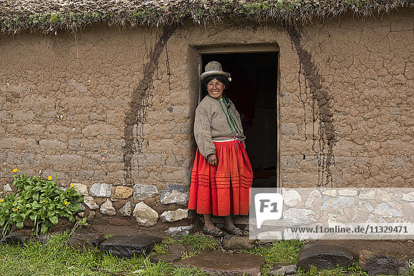 native woman in front of her house in Peru