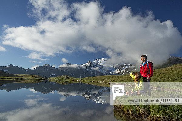 Couple hiking at Gibidumsee lake in Valais