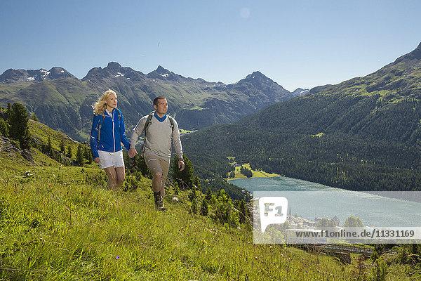 Couple hiking on Corviglia over Saint Moritz lake  Grisons