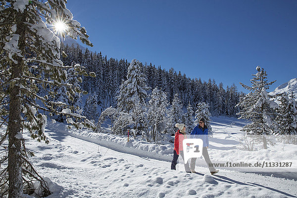 Couple walking at Statzersee near Saint Moritz in winter in Grisons