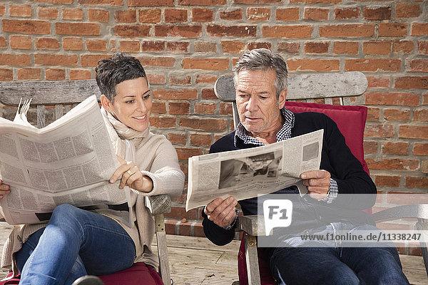 Mann zeigt der Frau eine Zeitung  während er im Garten sitzt.