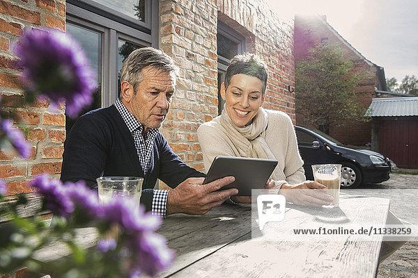 Erwachsenes Paar sitzend mit digitalem Tablett und Kaffee im Hinterhof