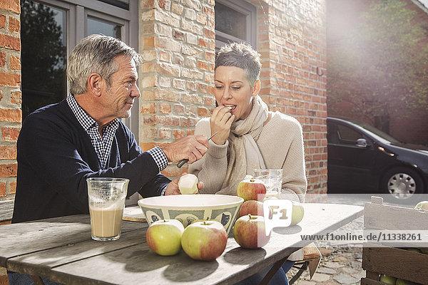 Reife Paare essen Äpfel im Hinterhof