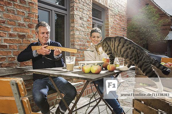 Verspielter Mann mit Spielzeuggewehr auf Tabbykatze beim Sitzen mit Frau im Hinterhof