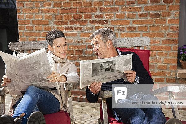 Mann zeigt Zeitung der glücklichen Frau  während er im Hinterhof sitzt