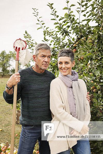 Porträt einer glücklichen Frau mit Mann im Apfelgarten