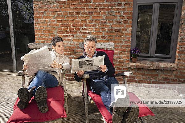 Ein reifes Paar liest Zeitung und sitzt im Garten.