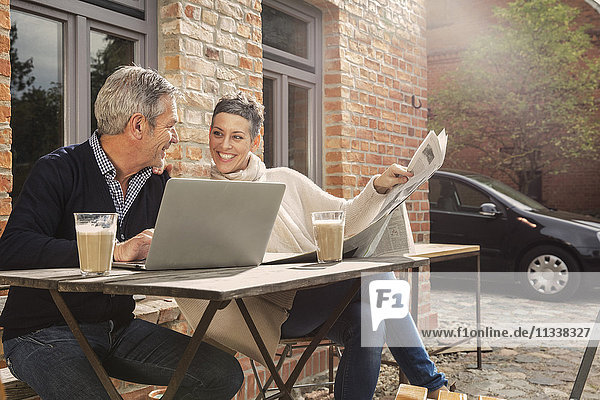 Fröhliches reifes Paar liest Zeitung mit Laptop im Hinterhof
