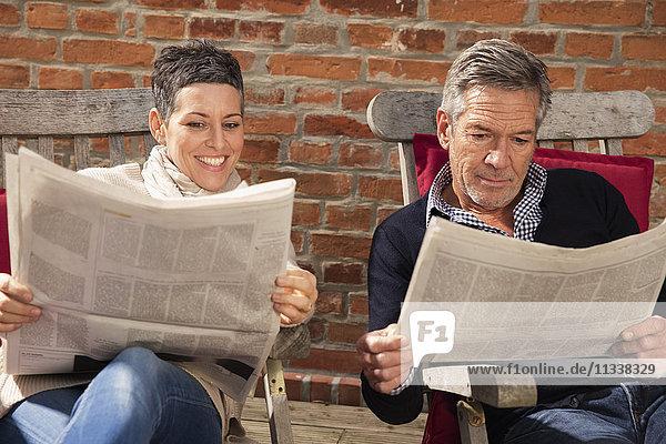 Glückliches Paar liest Zeitung gegen die Ziegelwand im Hinterhof