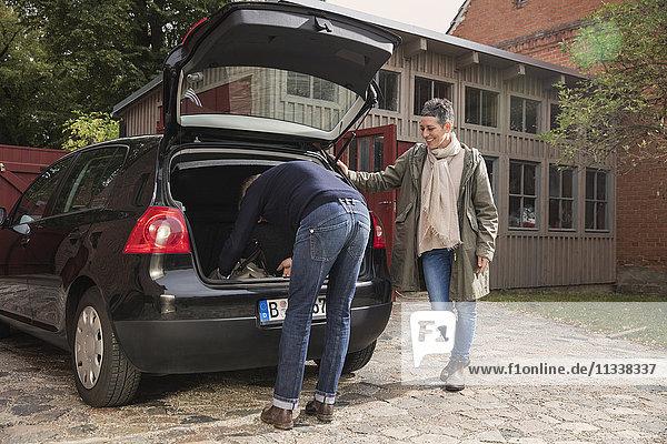Frau beobachtet Mann beim Packen von Gepäck im Kofferraum