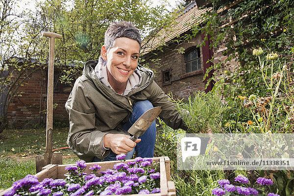 Porträt einer glücklichen Frau  die im Garten arbeitet.