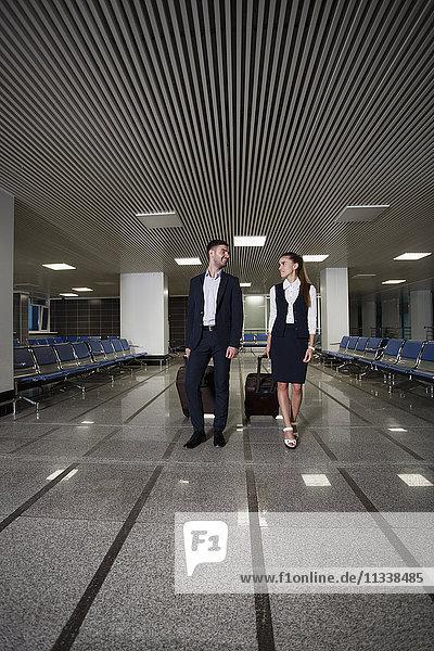 Volle Länge des jungen Geschäftsmannes und der Geschäftsfrau mit Gepäck  das im Flughafen läuft.
