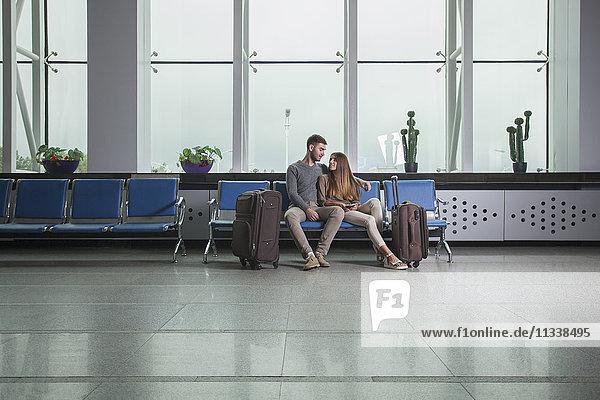 Junges Paar mit Gepäck auf Stühlen am Flughafen