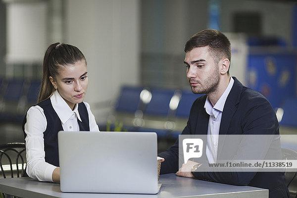 Junger Geschäftsmann und Geschäftsfrau mit Laptop am Flughafen