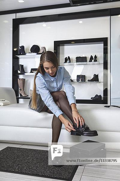 Volle Länge der jungen Frau beim Anprobieren von Schuhen im Laden