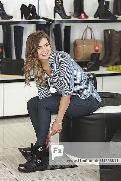 Glückliche Frau schaut weg  während sie Schuhe anprobiert.