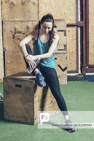 Volle Länge der Athletin  die die Wasserflasche hält  während sie in der Turnhalle auf einer Holzkiste sitzt.