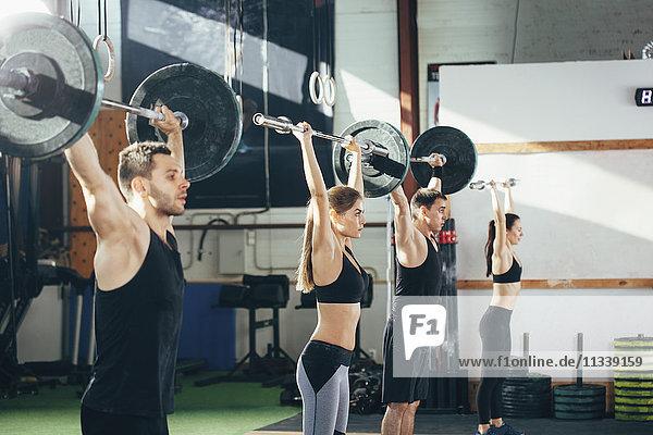 Seitenansicht der Sportler beim Heben von Hanteln im Fitnessstudio